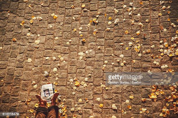 Low Section Of Person Resting On Cobbled Street