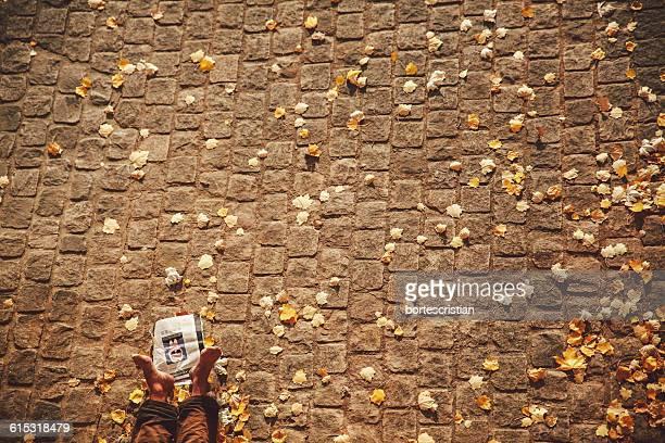 low section of person resting on cobbled street - bortes fotografías e imágenes de stock
