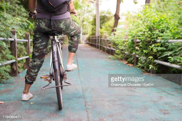 Low Section Of Person Riding Bicycle On Footpath