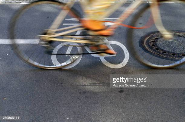 low section of person riding bicycle on road - pedal stock pictures, royalty-free photos & images