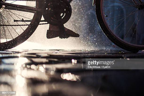 Low Section Of Person Riding Bicycle On Street In Rainy Season