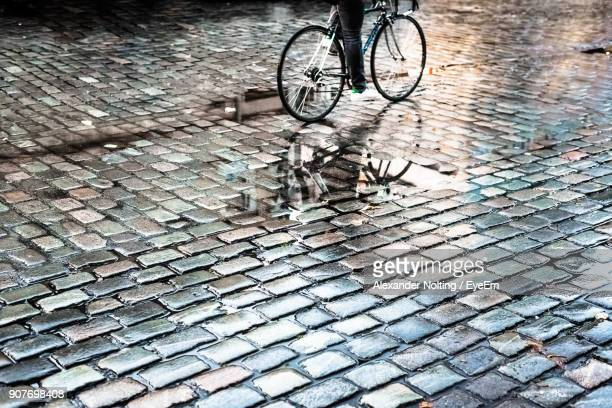 low section of person riding bicycle on wet road - unterer teil stock-fotos und bilder