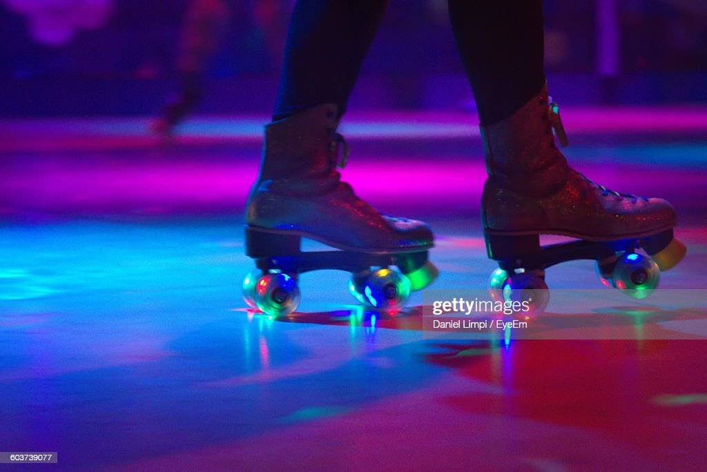 Low Section Of Person Roller Skating On Floor In Illuminated Rink : Stock Photo