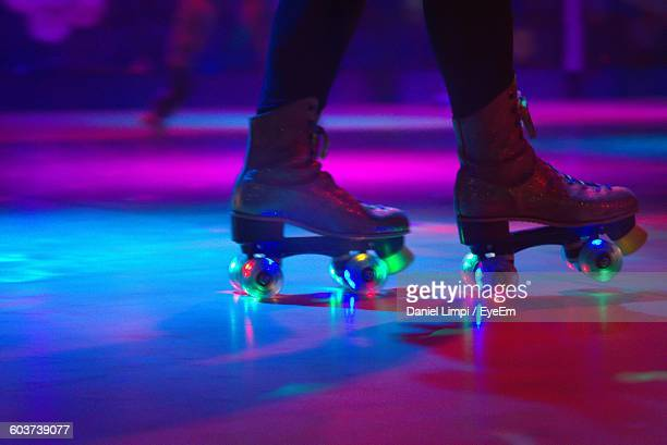 low section of person roller skating on floor in illuminated rink - patinar - fotografias e filmes do acervo