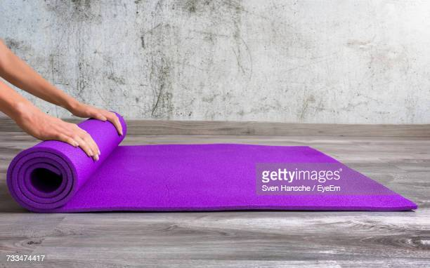 low section of person rolling yoga mat - yogastudio stock-fotos und bilder