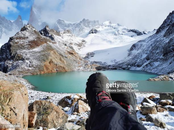 low section of person sitting against lake and snowcapped mountains during winter - chalten stock pictures, royalty-free photos & images