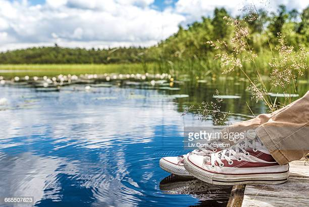 Low Section Of Person Sitting Beside Pond