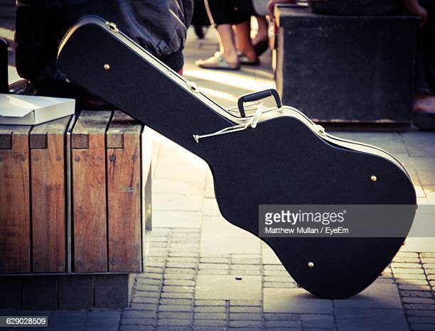 low section of person sitting on chair - guitar case stock pictures, royalty-free photos & images