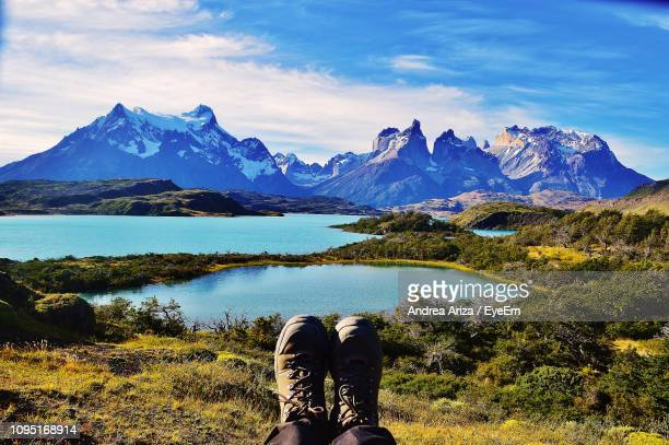 Low Section Of Person Sitting On Field By Lake Against Snowcapped Mountain