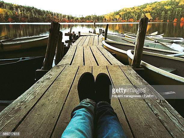 Low Section Of Person Sitting On Pier At Lake