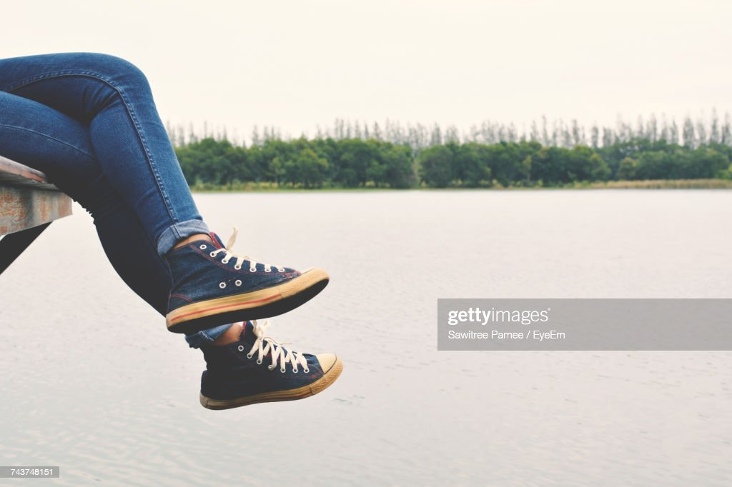 Low Section Of Person Sitting On Pier Over Lake : Stock Photo