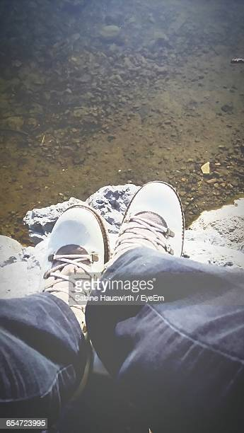 low section of person sitting on rocks by lake - sabine hauswirth stock pictures, royalty-free photos & images