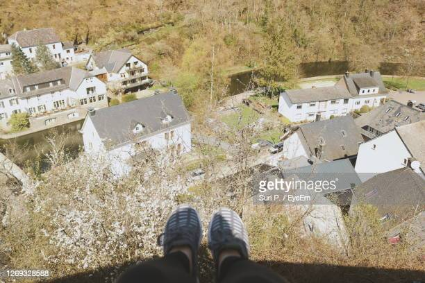 low section of person sitting on the wall overlooking the town - esch sur alzette stock pictures, royalty-free photos & images
