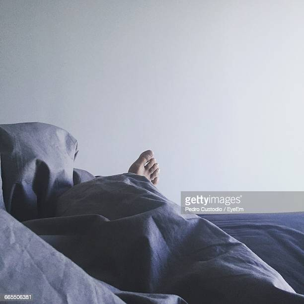 low section of person sleeping on bed against white wall - arab feet photos et images de collection