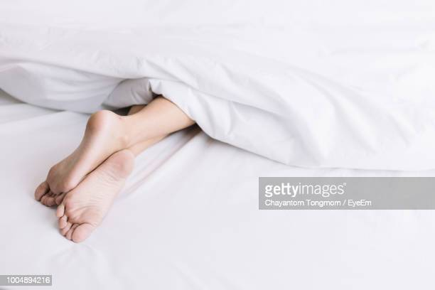 low section of person sleeping on bed - sheet bedding stock photos and pictures