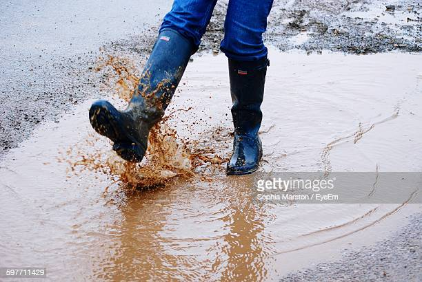 Low Section Of Person Splashing Dirty Water In Puddle