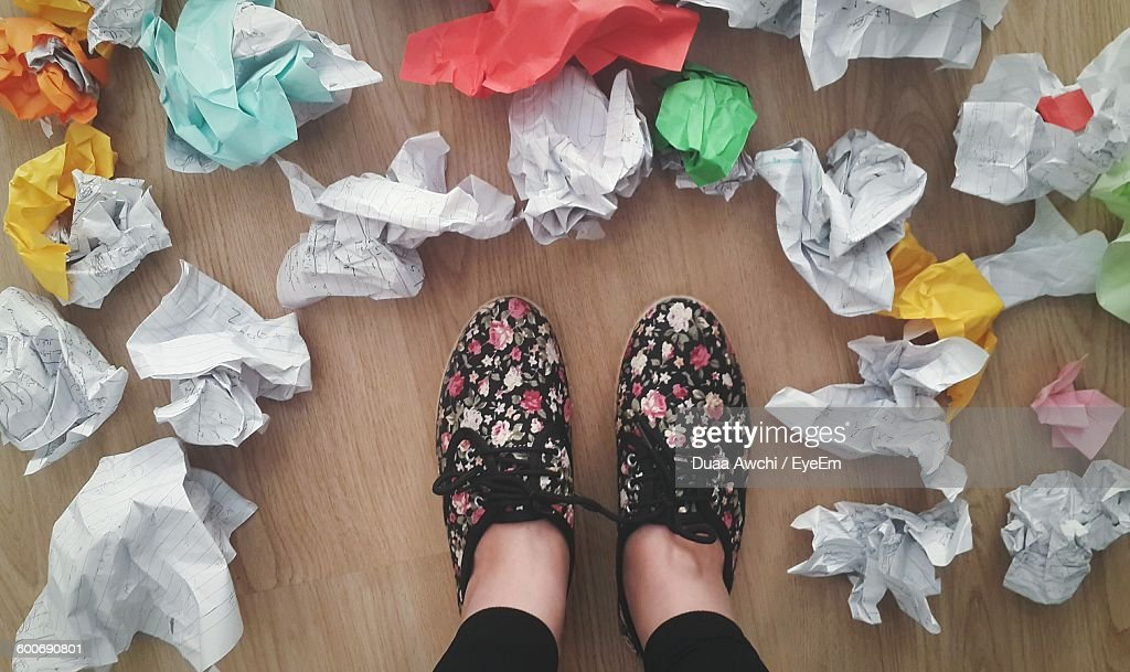 Low Section Of Person Standing Amidst Crumpled Paper Balls On Floor : Stock Photo
