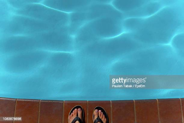 low section of person standing at swimming pool - paulien tabak stock-fotos und bilder