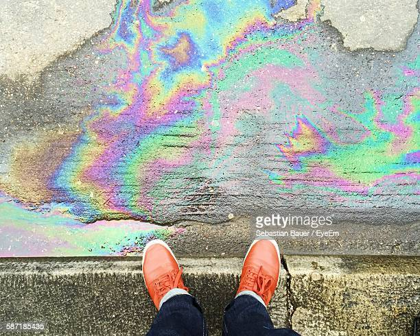 Low Section Of Person Standing Beside Oil Spill On Road