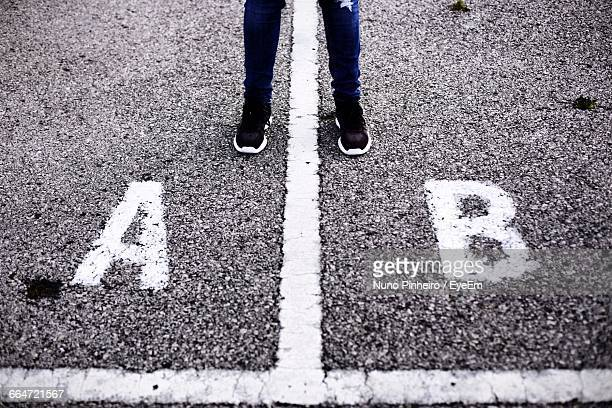low section of person standing by alphabets on street - letra b imagens e fotografias de stock