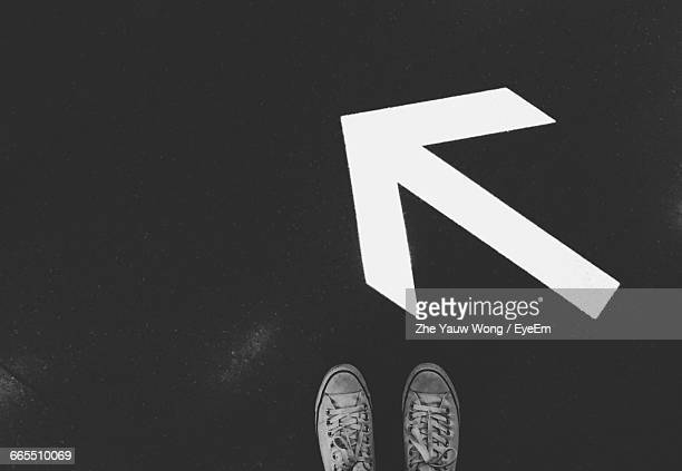 Low Section Of Person Standing By Arrow Symbol On Street