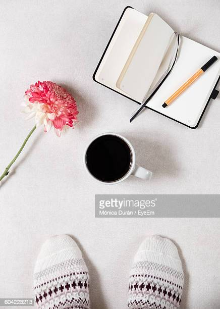 Low Section Of Person Standing By Black Coffee And Diary With Pen On White Background