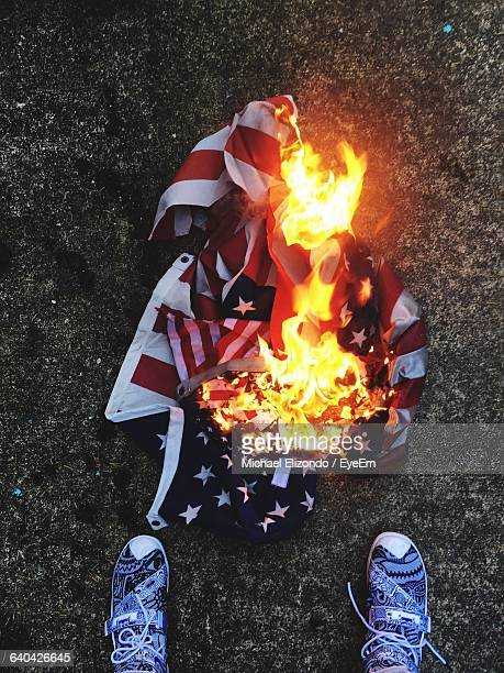 Low Section Of Person Standing By Burning Flag
