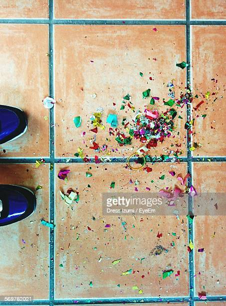 Low Section Of Person Standing By Confetti On Tiled Floor