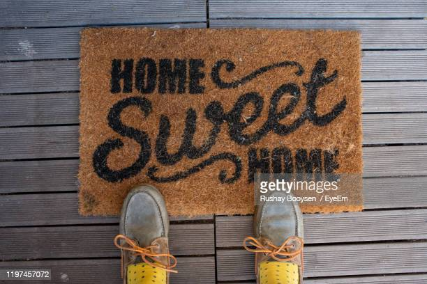low section of person standing by doormat with text on wooden floor - human doormat foto e immagini stock
