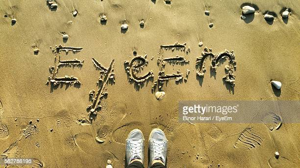 Low Section Of Person Standing By EyeEm Text On Sand