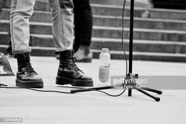 low section of person standing by microphone stand on floor - マイクスタンド ストックフォトと画像