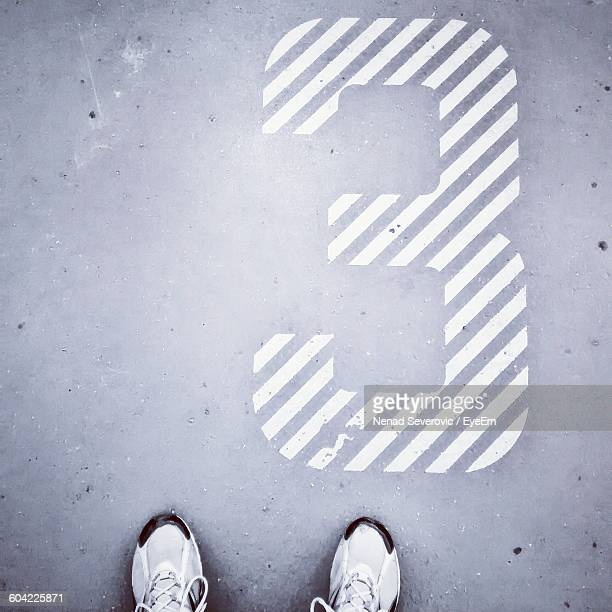 Low Section Of Person Standing By Number On Street