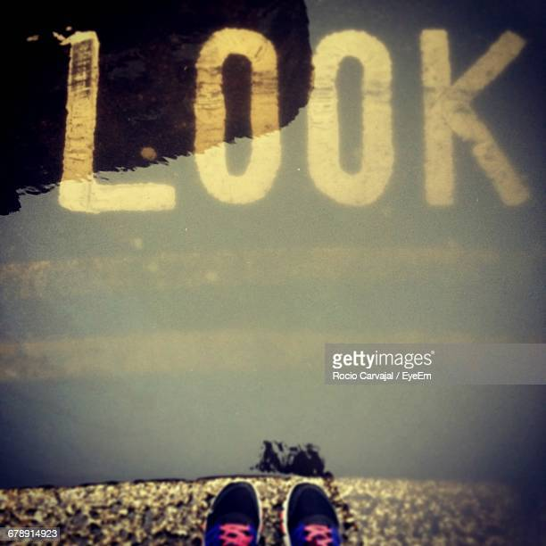 low section of person standing by puddle on street - carvajal stock photos and pictures