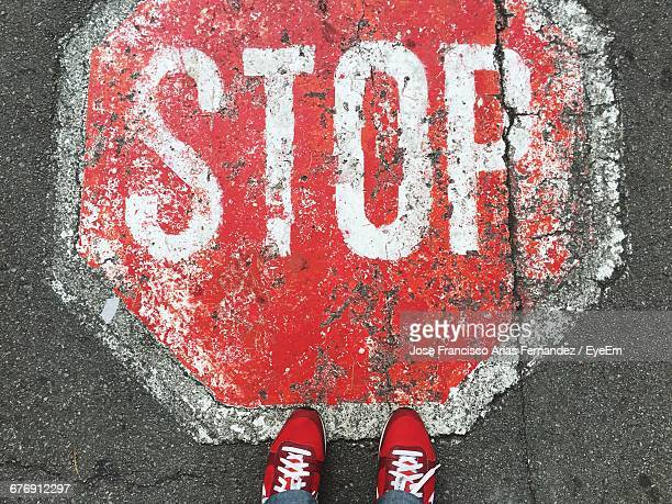 Low Section Of Person Standing By Stop Sign On Footpath