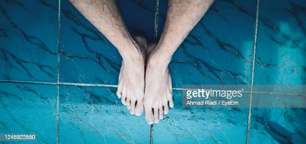 low section of person standing by swimming pool - 人のつま先 ストックフォトと画像