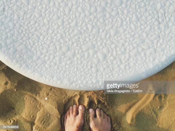 low section of person standing by wet white table at beach - viewpoint stock pictures, royalty-free photos & images