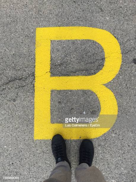 Low Section Of Person Standing By Yellow Letter B On Footpath