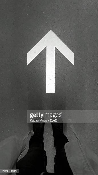 Low Section Of Person Standing In Front Of Arrow Symbol On Street