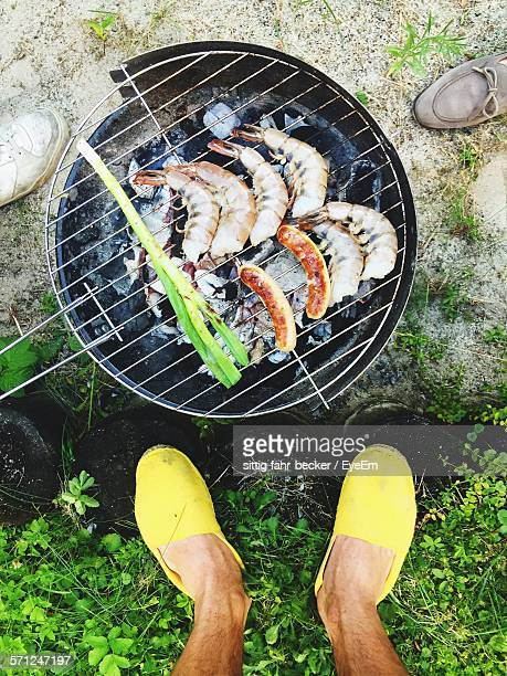 Low Section Of Person Standing In Front Of Barbeque