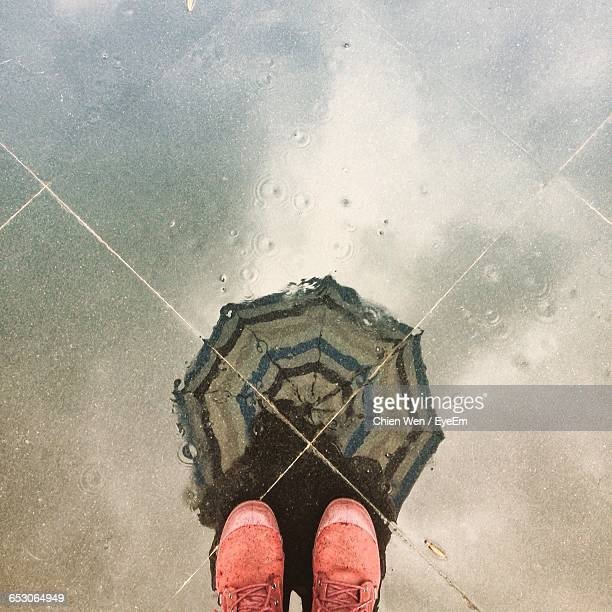Low Section Of Person Standing In Front Of Puddle