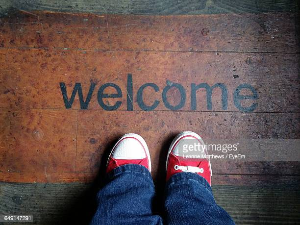 Low Section Of Person Standing In Front Of Welcome Sign On Wood