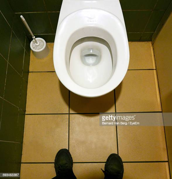 Low Section Of Person Standing In Toilet