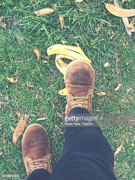 Low Section Of Person Standing On Banana Peel At Grassy Field