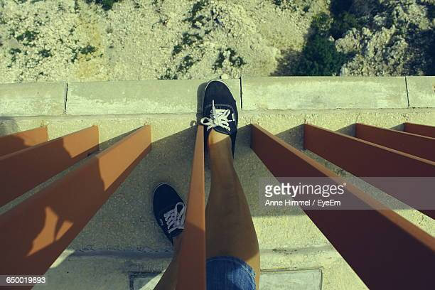 Low Section Of Person Standing On Bridge During Sunny Day