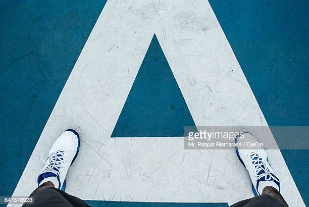 low section of person standing on court - blue shoe stock pictures, royalty-free photos & images