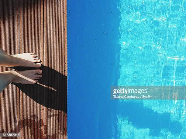 Low Section Of Person Standing On Diving Board