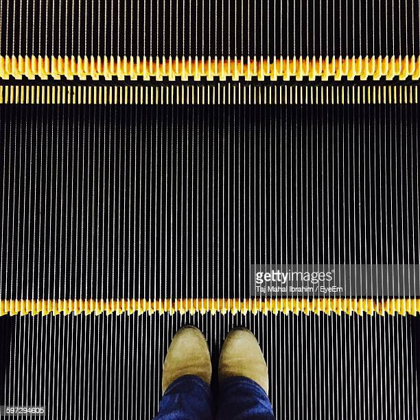 Low Section Of Person Standing On Escalator