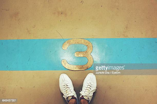 low section of person standing on floor by number 3 - terceiro lugar - fotografias e filmes do acervo
