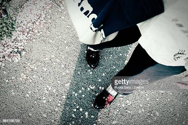 low section of person standing on footpath with fallen petals - loafers stock pictures, royalty-free photos & images