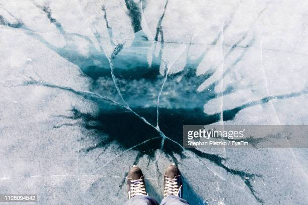 low section of person standing on frozen lake during winter - mujeres fotos stock pictures, royalty-free photos & images